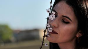 Ragazza ad occhi chiusi annusa un rametto fiorito