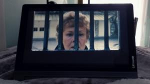 Una donna anziana si affaccia alle sbarre di un cancello